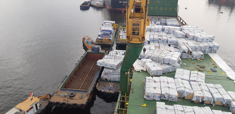 Выгрузка пакетов с пиломатериалами с палубя судна на лихтеры