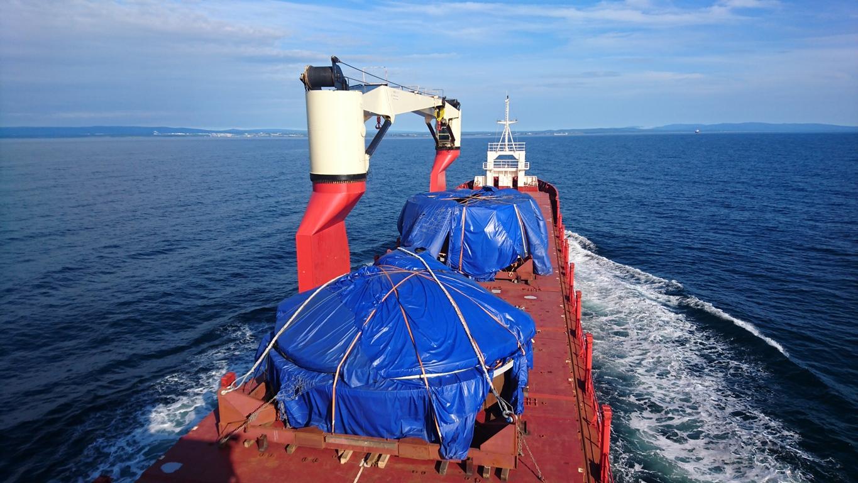 зачехленные секции вакуумной камеры на палубе судна.